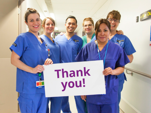 Hospital staff holding sign that says 'Thank you!'