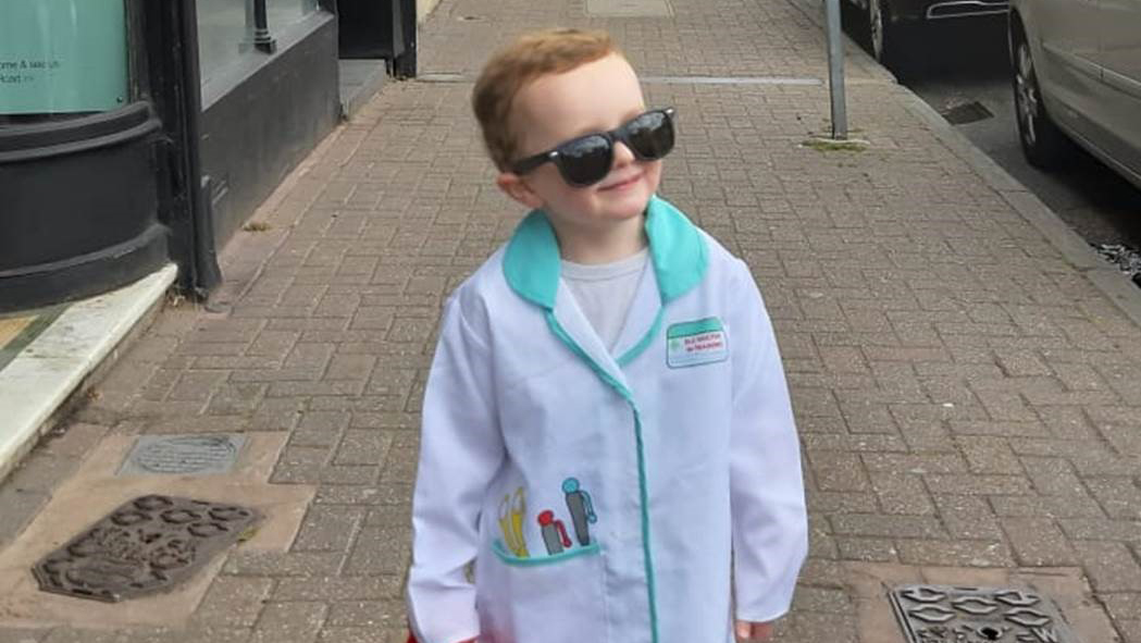 3-year-old fundraiser Hugo walks down the street dressed in a white doctor's coat.