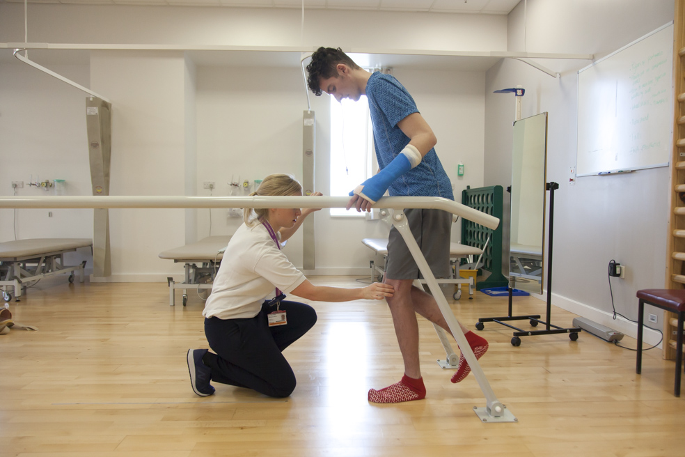 Nurse helps trauma patient with physiotherapy