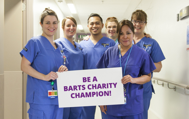 Hospital staff holding sign that says 'Be a Barts Charity Champion!'