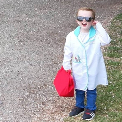 Small child dressed as a doctor for his fundraising walk