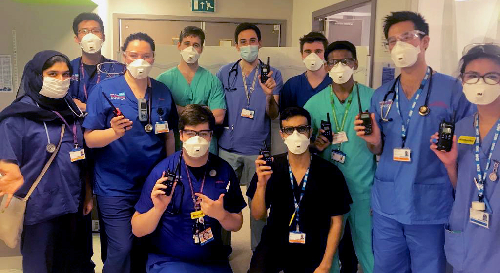 Large group of NHS staff wearing masks and holding up walkie-talkies funded by Barts Charity
