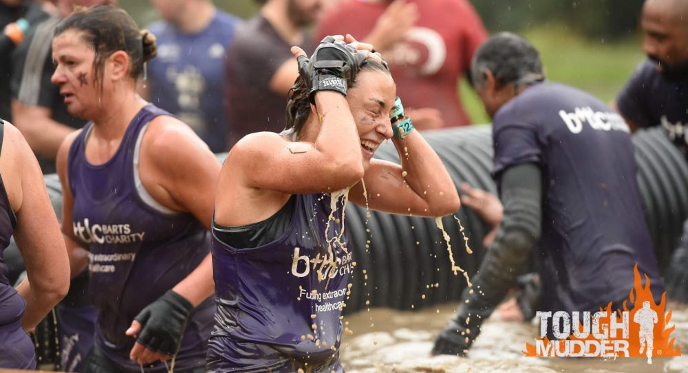 Woman covered in mud but grinning while taking on Tough Mudder