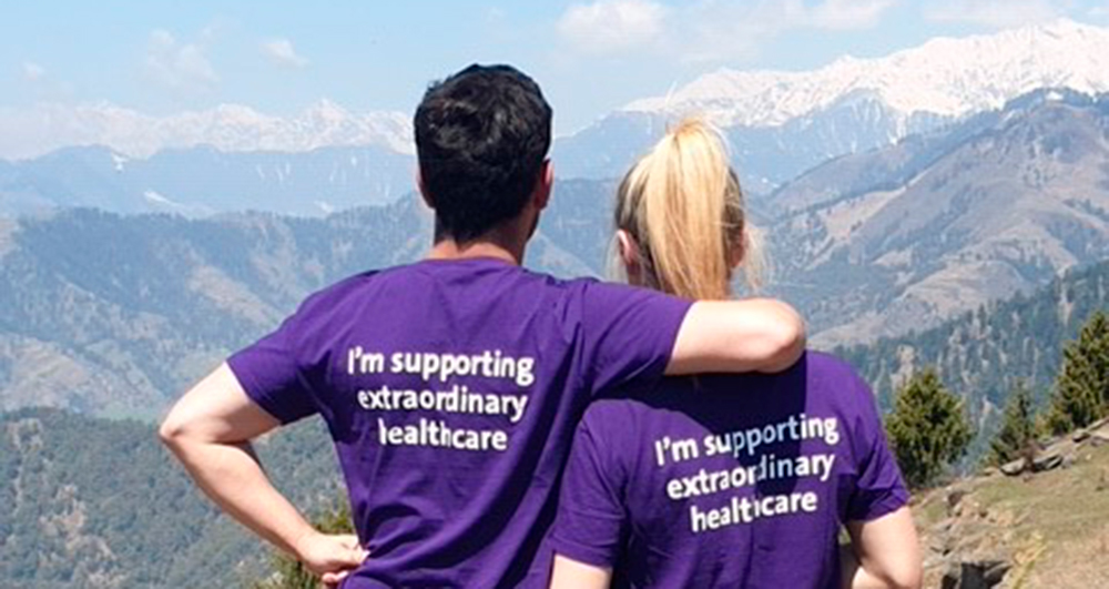 Two Barts Charity fundraisers silhouetted against the mountains they are trekking through